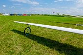 foto of glider  - Sailplane glider airplane wide angle shot on the ground field waiting for take - JPG
