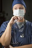 Concerned Female Doctor or Nurse Wearing Protective Face Mask and Holding Protective Eye Glasses.