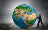 Businessman pushing big Earth planet. Elements of this image are furnished by NASA