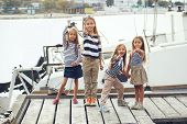 Group of fashion kids sailors wearing navy clothes in marine style enjoying in the sea port