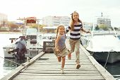 Fashion kids wearing navy clothes in marine style running on wooden berth near the sea