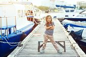 Fashion child wearing navy clothes in marine style posing on wooden berth in sea port