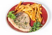 Swordfish steak cooked on a plate with french fries and a parsley and garlic butter sauce seen from the side