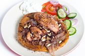 Musakhan, traditional Palestinian sumac chicken, on a plate with a salad and yoghurt,