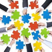 Group of Hands Holding Colorful Jigsaw Pieces