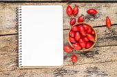 Wild Berries With Blank Notebook On Wooden Table.