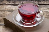 Cup Of Red Karkade Tea With Book On Wood Background