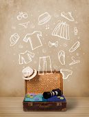 Traveler luggage with hand drawn clothes and icons on grungy background