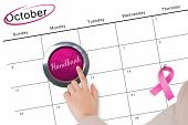 Hand pushing pink button for breast cancer awareness on october calendar