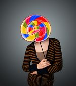 Young lady holding a colorful striped lollipop in front of her head