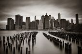 Manhattan financial district with skyscrapers and abandoned pier over East River in BW.