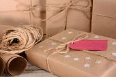 Closeup of a group of Christmas packages wrapped with plain brown paper and twine. Horizontal format on a wood table. A red gift tag and paper stars adorn one parcel.