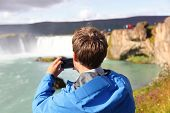 Tourist taking photo with smartphone of waterfall Godafoss on Iceland. Man taking picture with smart phone camera on travel visiting tourist attractions and landmarks in Icelandic nature on Ring Road.