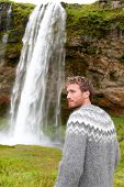Man in Icelandic sweater by waterfall on Iceland outdoor smiling. Portrait of good looking male model looking to side in nature landscape with tourist attraction Seljalandsfoss waterfall on Ring Road.