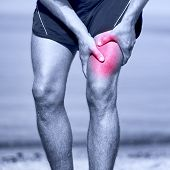 Muscle sports injury of male runner thigh. Running muscle strain injury in thigh. Closeup of runner touching leg in muscle pain.