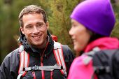 Male hiker portrait in forest talking with woman wearing backpack and jacket. Handsome man smiling candid during hike. Fresh male model in his 20s.