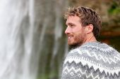 stock photo of waterfalls  - Handsome man in Icelandic sweater outdoor smiling by waterfall on Iceland - JPG