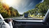 picture of steers  - Hands on steering wheel of a car driving on an asphalt road  - JPG