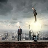Businessman standing on bulb and looking down at colleague