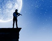 Young man playing violin at night under moon light