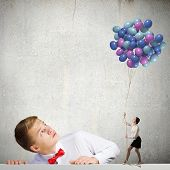 Businessman looking at woman holding bunch of colorful balloons