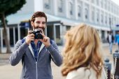 Man taking photo of girlfriend on holiday