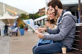 tourist couple sitting on bench looking at map