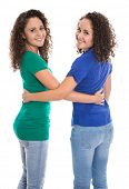 Portrait of an isolated couple of real twin sisters over white wearing blue and green shirt.