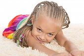 Cute little girl with dreadlocks lays on the mat. Girl six years.