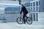 active businessman riding a bicycle on the way to job