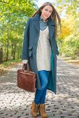 Pretty Young Woman Holding Leather Bag in Autumn Season Attire Posing at Pathway