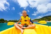 Little girl enjoying paddling in colorful yellow kayak at tropical ocean water during summer vacation