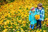 Two adorable kids outdoors in a beautiful park at sunny autumn day