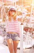 Luxury photo shoot on sailboat, cute blond model posing in mild yellow sunset light, summer vacation concept