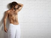 Picture of man in towel and brick wall behind.