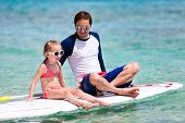 Father and his adorable little daughter sitting on stand up board having fun during summer beach vacation
