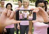 Composite image of hand holding smartphone showing photograph of breast cancer activists