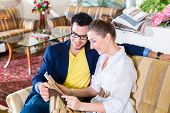 Young couple selecting together seat cover for sofa in furniture store