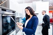 Woman picking oven for domestic kitchen in studio or furniture store