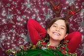 Festive little girl wearing antlers against snowflake wallpaper pattern