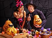 Man and woman on Halloween party  sitting at trick or treat table.