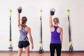 stock photo of kettlebell  - Two young women are doing shoulder presses with kettlebells - JPG