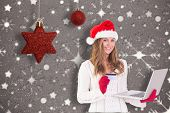 Festive blonde shopping online with laptop against snowflake wallpaper pattern