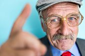 Portrait of a smiling and confident senior good looking business man with finger