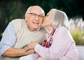 Senior woman kissing on man's cheek while sitting at nursing home porch