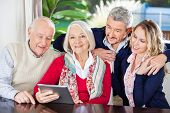 Portrait of smiling senior woman using digital tablet with family at nursing home