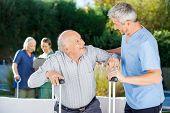 Male and female caretakers helping elderly people in nursing home