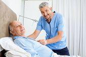 Portrait of smiling male caretaker examining senior man in bedroom at nursing home