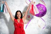Woman standing with shopping bags against blurred christmas decorations
