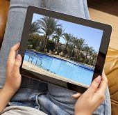 Cropped image of woman looking at resort photo on tablet